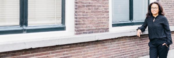 Foto van Eva Westerhoff, Eva leunt met arm tegen muur